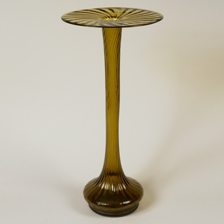 Tall, yellow-tinted glass form with flat disc-like rim at mouth, long thin neck, and circular base; engraved wavy vertical lines cover form.