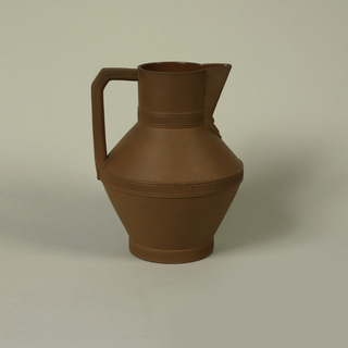 Angular pitcher form with three horizontal bands at the base, center--the jug's widest part--and the top third; angular handle.
