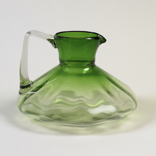 The undulating circular bowl with broad lower section rising to a cylindrical neck with the lower part in clear glass gradually changing to a deep emerald green at the neck and pinched spout, the right-angled clear handle terminating in an asymmetrical ridged curve.