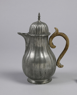 On shaped, flaring foot a pyriform body with grouped vertical gadrooning. Spout attached to body and decorated with incised lines and relief bands. Hinged domed cover with tall finial. Wooden handle with spur attached with pegs.