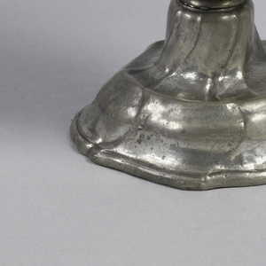 Shaped octagonal foot (probably used with another vessel originally); body in two parts, the lower bowl-shaped, the upper flaring and having a shell and scroll relief around the irregular edge. Double-scrolled foliated handle.