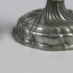 Gadrooned foot, baluster stem and flaring candle holder.