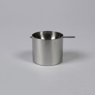 Ashtray of two parts: circular, stainless steel concave bowl (a) rests on lip of short cylindrical base (b); one short and one long steel pin project from opposite sides of bowl, and rest in grooves in lip of base.  (Bowl can be tipped by grasping and turning longer pin.)