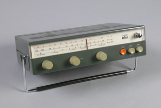 Flat rectangular grey-green plastic housing. Transparent window on front, six buttons below, metal telescopic antenna on right. Metal handle with black plastic cover, following the contours of the front. Holes for plugs on left side and bottom container for six batteries.