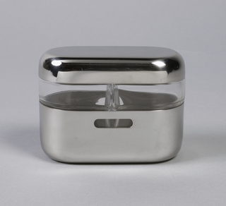 Polished, oval stainless steel cruet stand (a) with straight sides and flat base; narrow horizontal holes pierced in front and back; containing pair of molded clear glass cruets (b,c) surmounted by oval stainless steel cover (d).