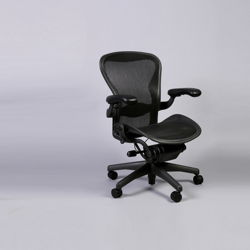 Task chair of black mesh stretch fabric within black frame consisting of contoured back, broad contoured seat with sloping front edge, adjustment mechanism under seat; black, adjustable padded arm supports; base consisting of vertical post on five radiating feet with casters.