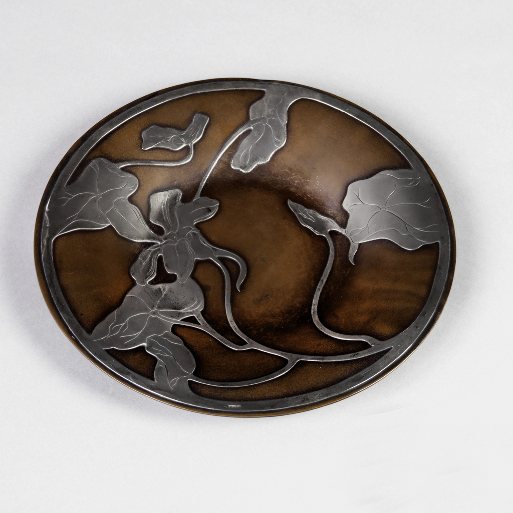 Circular copper plate with design overlaid in silver of leaves, vines and flower.