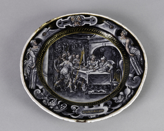 """Circular plate, decorated en grisaille, with flesh tones and heightened in gold, showing a scene of a couple banqueting; captioned """"Ianvarivs."""""""