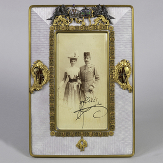 Rectangular frame, plain back with flat hinged scroll stand and flat hinged photograph cover. At front, plain gilt border surrounds wide band of mauve enamel with engine0turned decoration. Center of frame with rectangular beveled glass surrounded by gilt metal and enamel border composed of links and pendant fleece of the Order of the Golden Fleece. This border connected to outer frame by two scrollwork cartouches containing enameled coats of arms. Upper border of aperture frame applied with silver and gilt silver confronted winged gryphons, holding two silver and enamel crowns. Red leather fitted case with brown suede interior. Photograph of couple, male in military dress; photo signed in lower right.