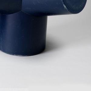 Squat blue form of cylindrical seat on tripod base.