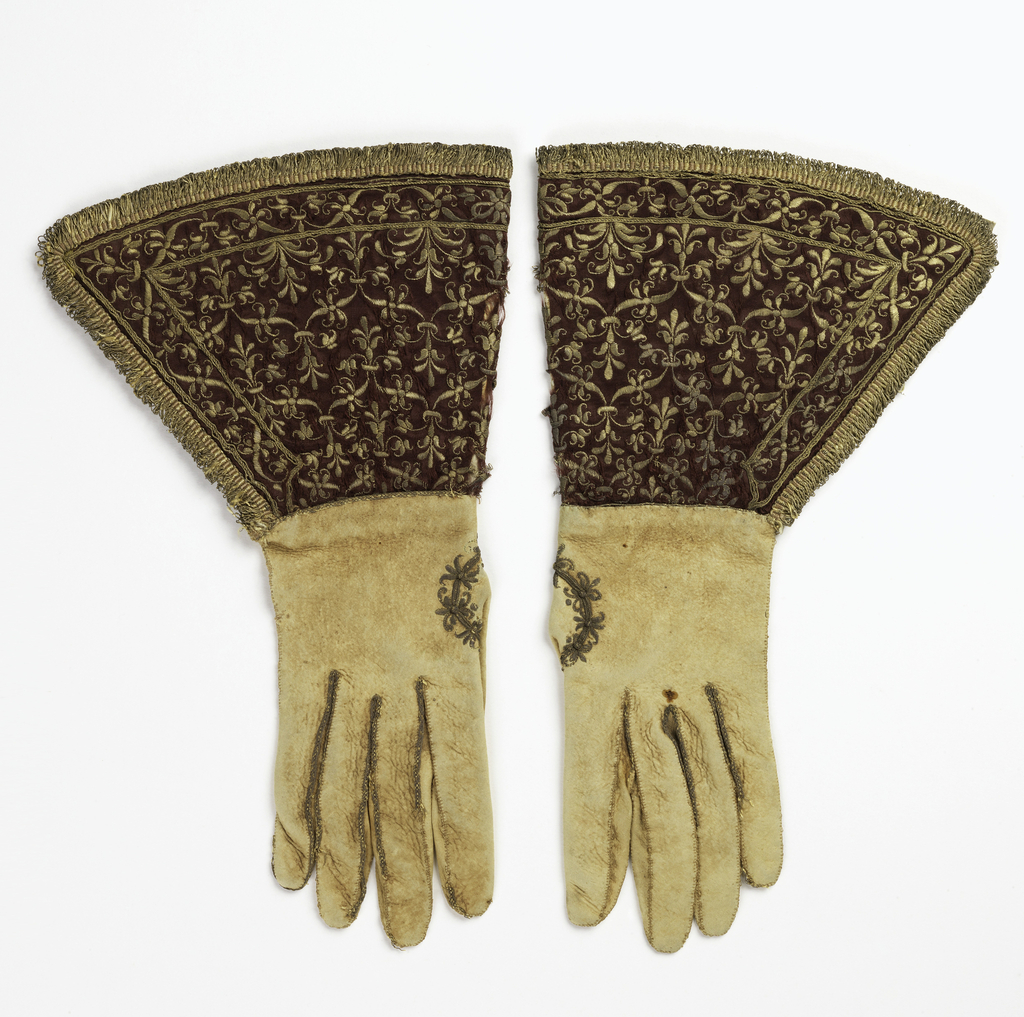 Pair of white leather gloves with deep gauntlets of dark red satin. The gauntlets are embroidered in gold metallic yarns with a small repeating design of a fleur-de-lis, and are edged with gold fringe. Lined with yellow silk.