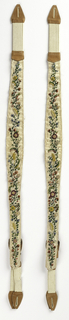 Leather suspenders decorated with multicolored floral design on a white ground.