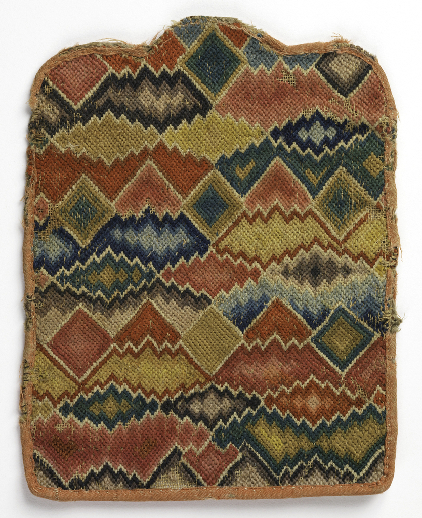 Envelope-style purse embroidered solidly in brilliantly colored wools in bargello or flame stitch. Reds, pinks and yellows predominate, with shades of blue, green and brown. Bound in light red tape.