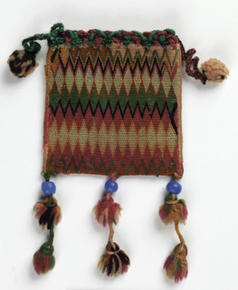 Small drawstring bag in a flame stitch pattern of red, orange, pink, black and green. Bottom edge of bag has three tassels with blue beads. Drawstring trimmed with multi-colored pompoms.