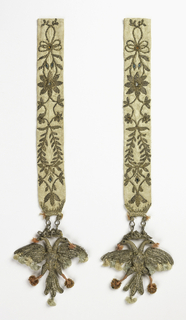 Pair of double-headed crowned eagles in needlework attached to white silk embroidered bands. Eagles, worked in the round, are of plaited gold thread. The wings, tails, and crowns are wire covered with looped silver wire. Colored silk tufts hang from beaks, claws, tails and wings. Silk bands embroidered with couched gold and glass jewels.