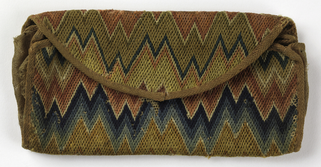 Envelope-shaped purse with flame stitch embroidery in wool in shades of red, blue, and brown. Lined with rose colored linen.