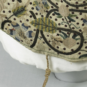 Woman's coif of off-white linen, with a point over the forehead, shaped at the cheeks, and with a pleated detail at the crown. Embroidered in light colored silks and metal threads with scrolling vines in silver metallic thread framing flower heads, among which appear caterpillars, bees and insects, embroidered in in red, pink, green, blue, yellow and gray silk. The ground is spotted with silver sequins stitched down with red thread.