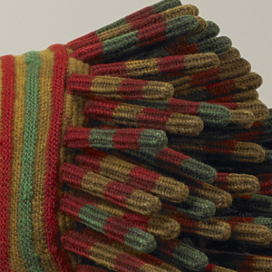 Orange, green, and yellow striped hat with a large cluster of finger-like projections or burls on each side. Each projection is also striped and the shape is reinforced with a wood splint. A small tassel hangs from the center back.