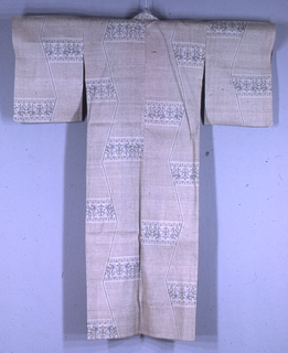 Kimono of natural colored raw silk  (tsumugi) with a small all-over geometric pattern in light brown. An elongated zigzag line divides each panel vertically. Horizontal bands have organic forms in a delicate palatte of blue and gray. The patterning technique is called yūki-tsumugi, or double ikat. The collar is faced with bright red silk.