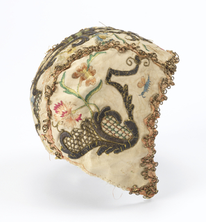 Cap for a baby made with a central section and two side pieces. Made of white taffeta with embroidery showing flowers and two insects and ornamental forms and metal thread. Edged with pink ribbon and metallic lace, lined with green silk. Two ribbon ties.