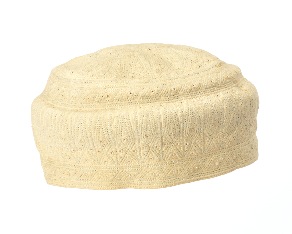 Circular cap quilted in geometric designs arranged in bands