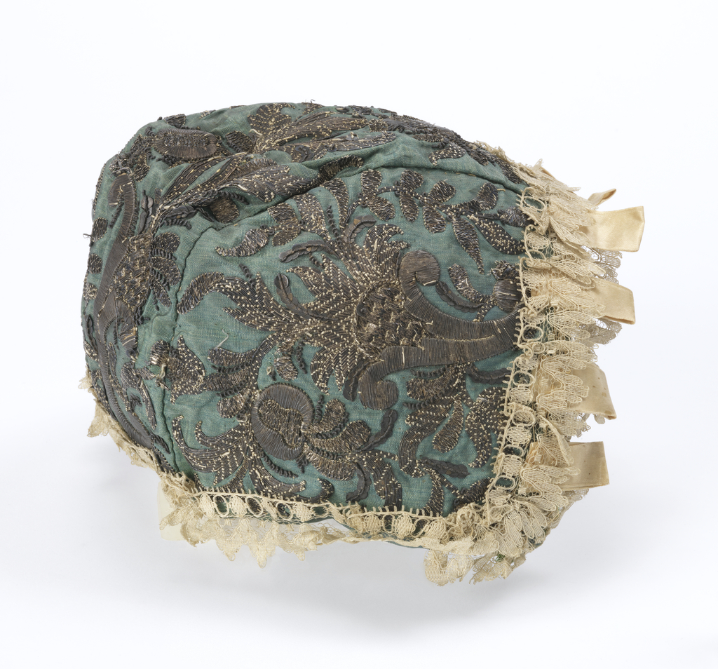 Bonnet of green silk with embroidery in silver thread. Lining of white silk and with ties of bright green ribbon with picots. edged with silk lace and satin tabs (added later).