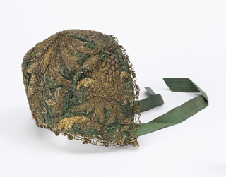 Bonnet of green silk embroidered in gilt thread and edged with gold lace. Lined with pink silk and has ties of green silk ribbon.