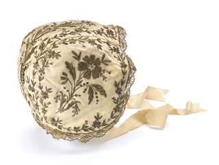 White satin bonnet with embroidery in gold thread and paillettes in design of flowers with leaves; gold lace around face opening. Ties of (faded) pink silk ribbon.