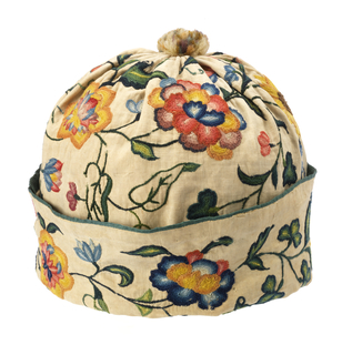 Off-white linen cap, gathered at the top and ornamented with a wool pompom; turned-up cuff edged with green silk binding. Embroidered all over with a curving vine with large exotic flowers in shades of blue, green, yellow and red wool.