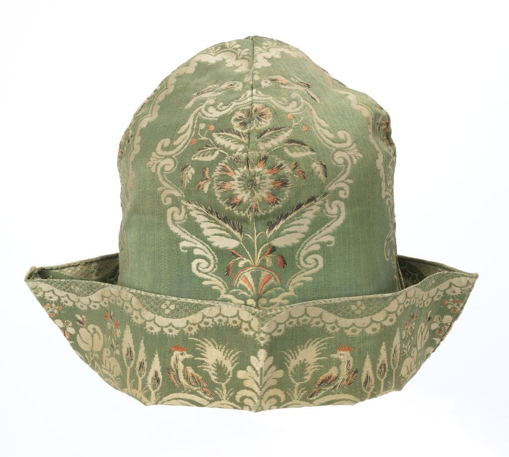 Man's nightcap with a rounded crown and turned-up brim. The fabric has a green silk satin ground with a woven pattern of flowers and arabesques in cream silk. The brim uses a different section of the same fabric, patterned with rabbits, fruit, trees, and addorsed birds.  Touches of salmon and silver embroidery accent both areas.