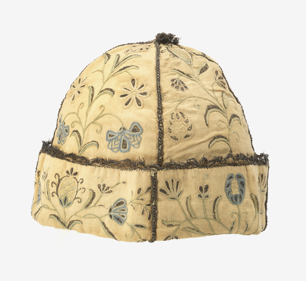 Cap of cream white cotton, made in four conical sections. Seams stitched in silver thread, joined at top with metal tassel. Embroidered with small-scale flower sprays in blue, white, and metal thread. Cuff embroidered in symmetrical pattern of pomegranate and foliage sprays.