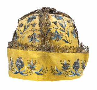 Man's cap of yellow silk taffeta made up of four panels with a deep turn-up cuff. Embroidered with symmetrical chinoiserie floral sprays in satin stitch in blue ombre silk, and in bouclé stitch in silver metallic yarns. With silver metallic bobbin lace covering the four seams and edging the cuff.