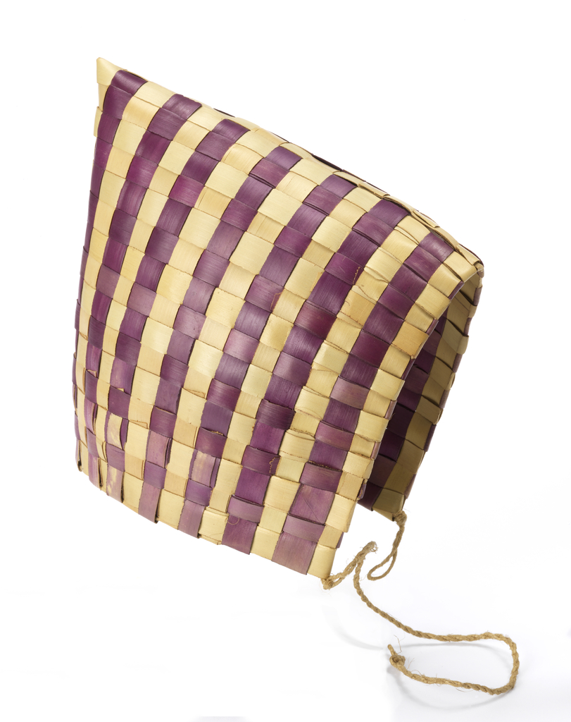 Cap with a slightly pointed peak. Square sides come to a point at either side of the chin where it is finished with a hemp cord to secure under the chin. Woven in broad flat rushes in a natural color and dyed magenta forming stripes.
