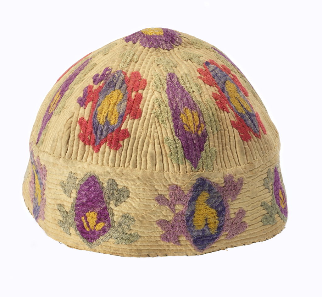 Cap decorated with long ovoids surrounded by stylized borders. Multicolored silks are embroidered using coarse satin stitch in purple, pink, yellow and green. Quilted cords make ridges that give stucture to the cap. Quilting radiates from crown and runs down to the rim band which is made from a separate piece with the ribs running around. Unlined except for a black oilcloth sweatband added more recently.
