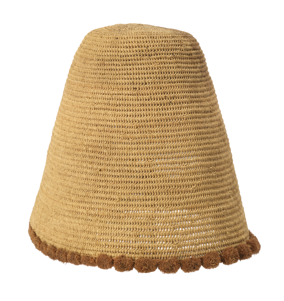 High conical hat in natural raffia with edging of small rust-colored raffia balls sewn on with buttonhole stitch.