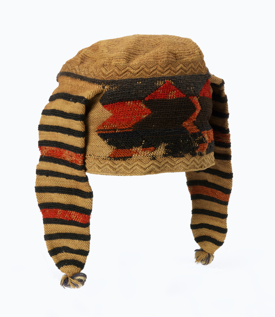 Cap of natural-colored raffia, with geometric triangle patterns in red and black wool around the band, and two horns dangling at the sides, striped with black and red. The crown is made in twisted looping. The band and horns are made in one, in overhand knotting technique with raised rows of knots for form the zigzag borders. The colored yarns are overlaid on the raffia during construction. Edge of lateral looping. Horns terminate in tassels of multicolored cotton.