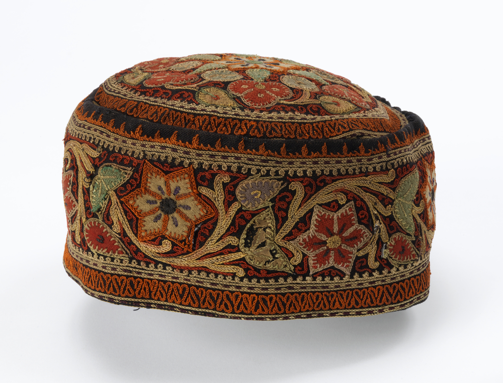 Small cap made of black wool with a floral design of multicolored appliqué and embroidery.