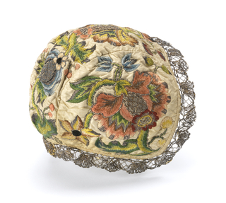 Infant's cap of silk embroidered in colored silks and silver metallic yarns. Pattern of heavy flowers, in reds, blues, greens, with centers and accents in metal. Gold bobbin lace edging.