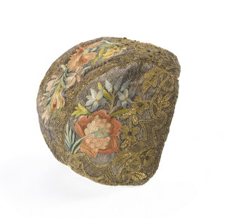 Christening cap embroidered in multicolored silk with gold and silver threads in a pattern of flower sprays on a ground of couched silver; bordered in gold.