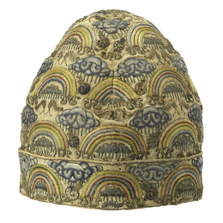 A man's cap with turned up cuff, of off-white linen embroidered in a pattern of rainbows arching over clouds with rain falling, with snails and caterpillars interspersed. In blue, green, yellow, red and pink silks and silver metallic yarns.