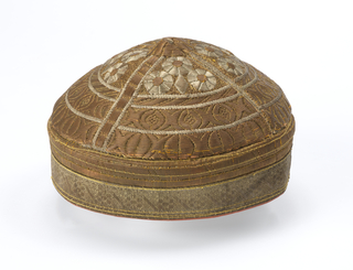 Men's cap solidly embroidered in gold and silver metallic threads with bands of small-scale geometric patterns.
