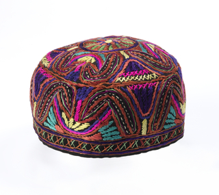 Small cap of black cotton twill embroidered in an allover multi-colored pattern.