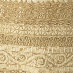 Man's cap of white linen with a deep cuff of alternating bands of embroidery in scrolling vine and stylized floral motifs, and needle lace in geometric patterns. Lace and embroidery silk in dark tan.