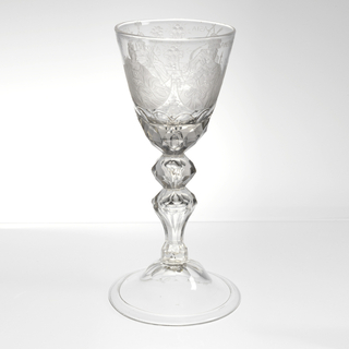 Deep flaring chalice, cut at bottom, and engraved with four semi-circles containing the Four Continents enthroned. Asia in turban, with basket of gems; Europe with scepter; Africa with feathered scepter and bird; America with feather cape and headdress, holding bow and arrow. Cut baluster stem and knob; domed foot, with cut top.