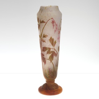 Tall flaring footed vase decorated with green and red leaves, pink flowers on white background. Inverted mouth, twisted stem, and orange-red bell foot.