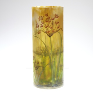 Cylindrical vase depicting plants and red flowers in a landscape of greens and yellows.
