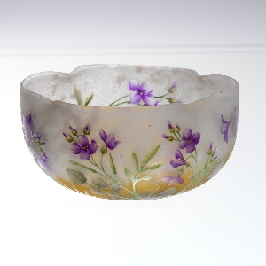 Frosted glass bowl decorated with plants and purple flowers. Irregular rim.