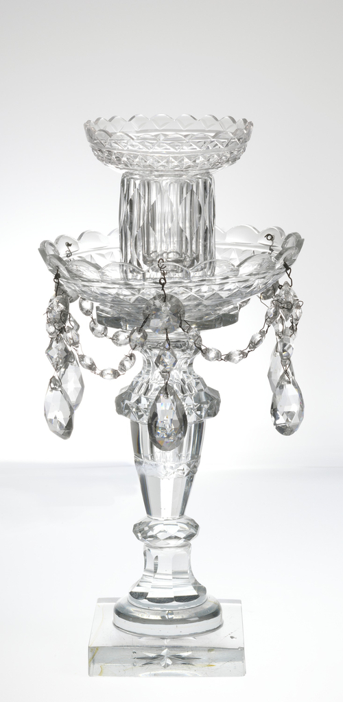 Glass candlestick with square base; a thin shaft near foot, with round drip pan with scalloped rim, garlands of beaded glass and hanging teardrops. Above this, straight wide shaft and open mouth for socket with small scalloped rim.