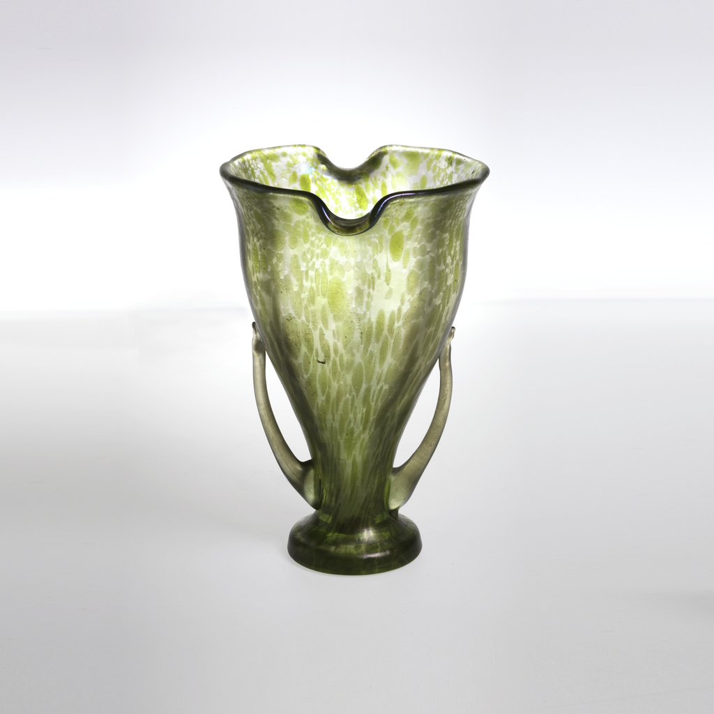 Mottled green footed glass with two handles.