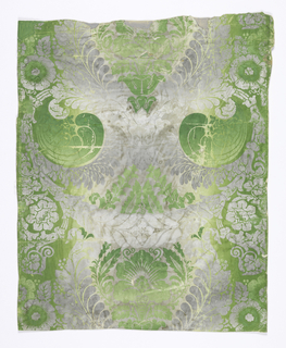 Gray and green irise or rainbow ground, overprinted with formal symmetrical pattern of scroll-work, leaves, flowers and swags in green, gray and white. Both the background and the printed design are in the rainbow or irise technique.